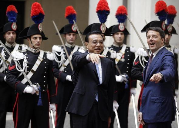 Italian Prime Minister Renzi gestures next to China's Premier Li as they arrives for a meeting at Chigi Palace in Rome
